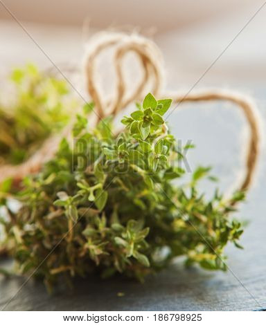 Freshly harvested herbs with old antique scissors on wood background.