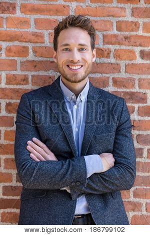 Happy smart casual businessman portrait on urban city brick wall background lifestyle portrait. Young professional man smiling confident in blazer. Career and entrepreneurship concept.