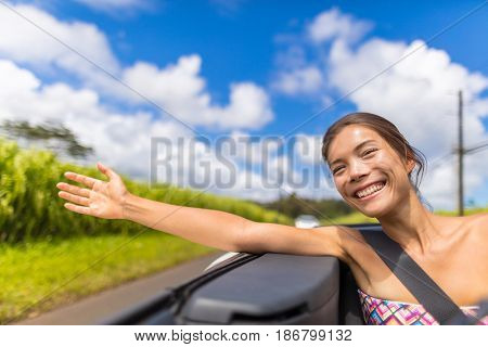 Car road trip woman freedom with hand floating in the wind. Asian girl sitting in convertible automobile carefree enjoying roadtrip holiday with arm sticking out of window concept.
