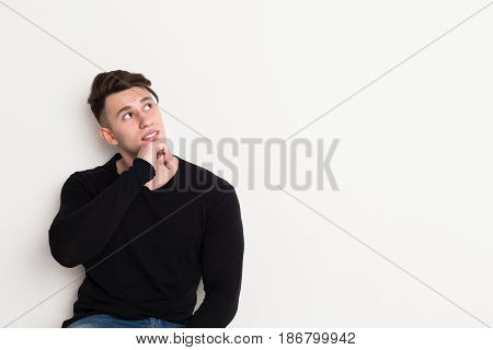 Pensive young man looks up, copy space at white background. Male portrait in casual at studio background.