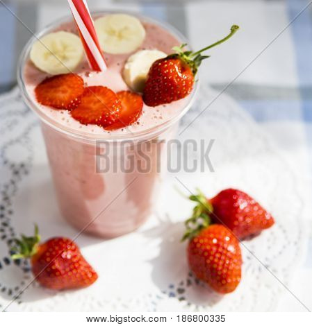 Strawberry-banana smoothie with milk or yoghurt. Healthy summer smoothies to go in a plastic cup