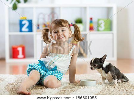 Lovely child girl and her pet dog in children room