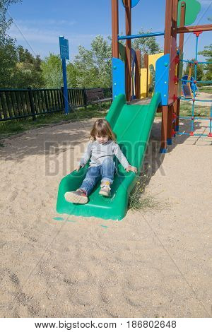 Kid Playing In Green Slide