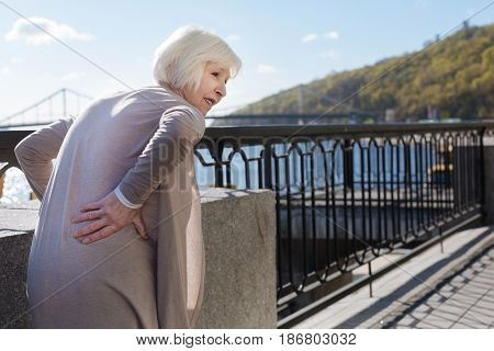 Unpleasant feelings. White haired nice puzzled pensioner standing and putting hand on her back while walking near the river