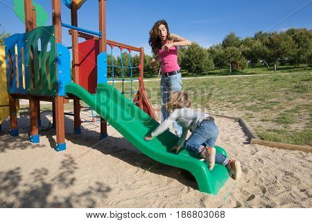 Mother Surprised By Child Sliding In Green Slide