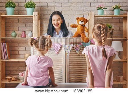 Happy loving family. Mother and her daughters in kids room. Funny mom and lovely children having fun and playing performance in the puppet theater indoors. Teddy bear.