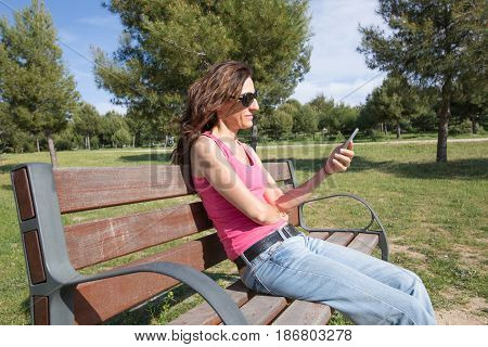 red hair woman with pink tank top shirt blue jeans and black sunglasses reading mobile phone smartphone sitting in a bench at public Park Valdebebas in Madrid Spain