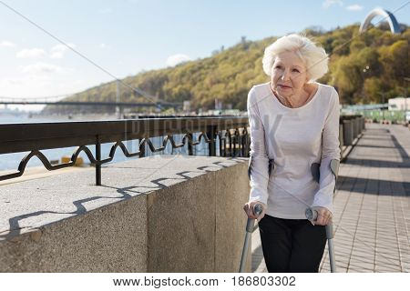 Years beginning to decline. Smiling lovely attractive woman being with crutches thinking about her life while strolling up