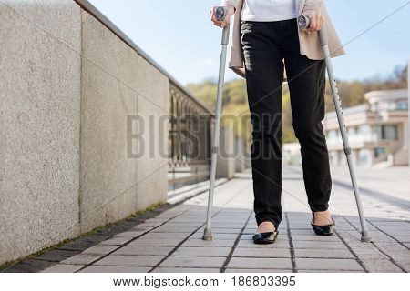 Heavy footsteps. Trendy involved shy lady holding crutches in her hands and making steps while going along the quay