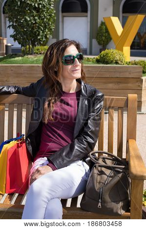 Portrait Of Woman Sitting In Bench With Shopping Bags And Purse