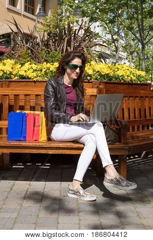 Woman In Bench Oudoors With Shopping Bags Typing In Laptop