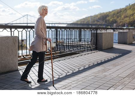 Move every day. Kind nice womanly lady taking though about birds and leaning on the stick while going straight on the promenade
