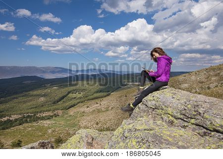Woman On Top Of Mountain Typing In Tablet