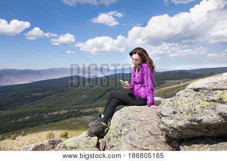 Woman On Top Of Mountain Watching Mobile Phone