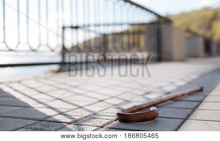 Important device for pensioners. Derelict wooden professional stick wallowing on the ground