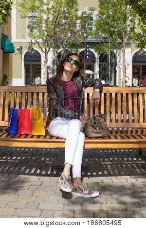 Woman Relaxing In Bench With Shopping Bags Vertical