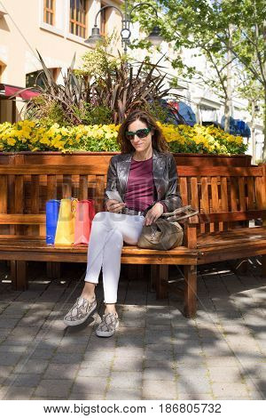 Woman Sitting In Bench With Shopping Bags Using Phone
