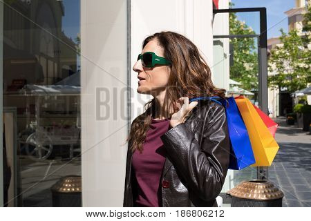 Woman With Shopping Bags Looking At Store Showcase