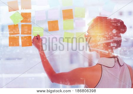 High angle view of illuminated cityscape against rear view of designer looking at sticky notes on glass