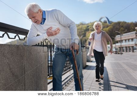 Unexpected pain can be dangerous. Weak upset neat man walking and expressing malaise while gentle woman speeding along to this man