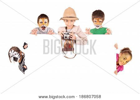 Children's group in safari clothes and animal face-paint over a white board