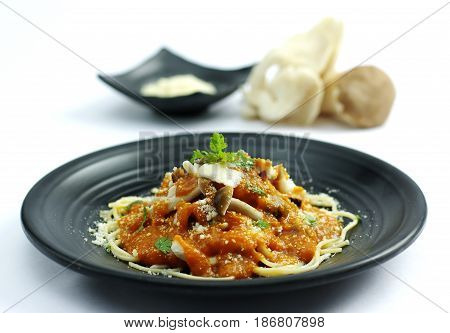 Sauteed Mushroom With Tomatoes Sauce And Ramen Noodle On Black Dish