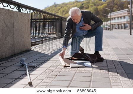 Daily routine. Friendly pleasant shy pensioner holding his hand on the chest and standing on the knee while packing his bag