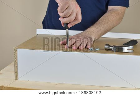 Man's hands screwing a wood screw in a drawer backside set on working table