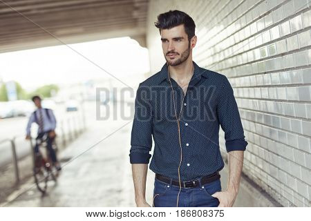 Handsome young man walking in underpass listening to music through earbuds.