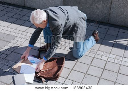 Lack of benches in the street. Aged good-looking educated man searching for documents putting his bad down while going to walk