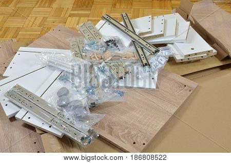 Pile of just unpacked elements of a new chest of drawers ready for assembling