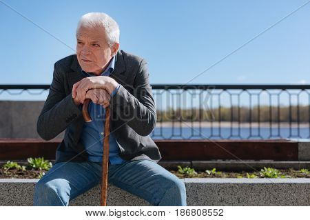 Years fell away. Old cagey sorrowful man sitting on concrete stab crossing his hands while looking at young people