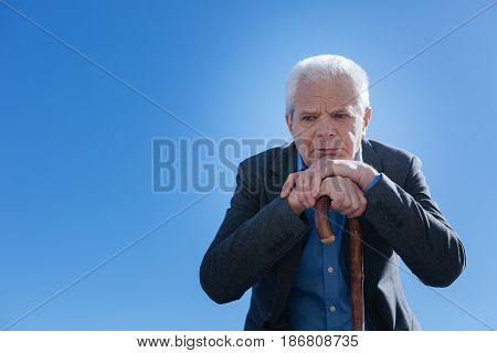 Life seems not so easy. Disappointed sick unhappy pensioner refreshing memories from his life and saddening while sitting in the park