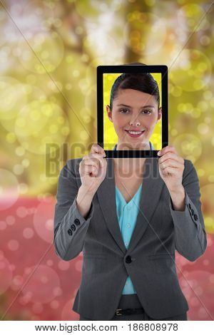 Businesswoman holding digital tablet against peaceful autumn scene in forest