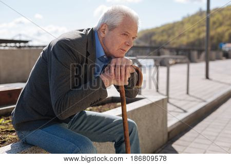 Take a break. Aged peaceful well-build man sitting on the flowerbed and holding his hands on the stick while having a rest