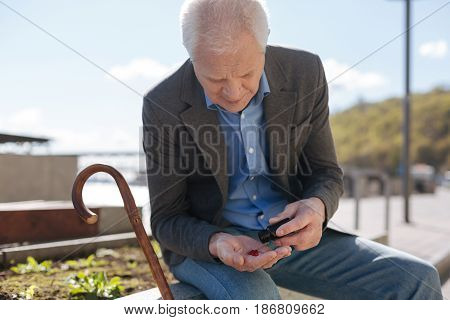 Taking care about my health. Happy good looking old gentleman putting down a stick and emptying the bottle with medicines while sitting on the flowerbed.