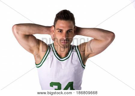 Studio shot of young man in basketball tank-top, stading isolated on white background, rising hands behind his head