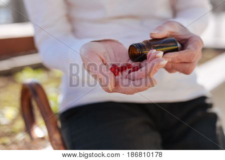 Medicine the best helper for old age. Neat aged diseased woman worrying about her health and using pills while having a rest