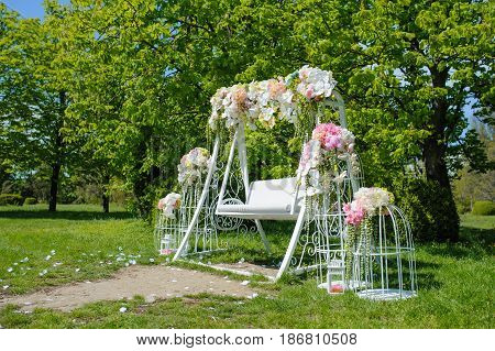 Wedding composition decoration in old vintage romantic style with white metal cages and nice swing