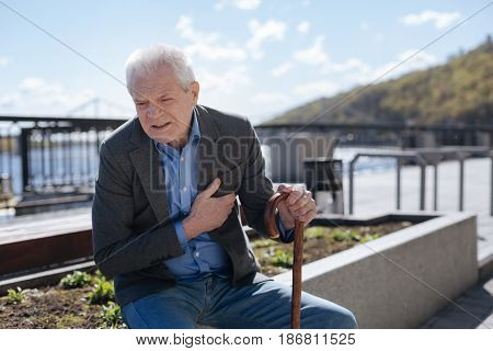Every day can be last. Retired scared sad pensioner holding his hand on the chest and worrying while waiting for a doctor