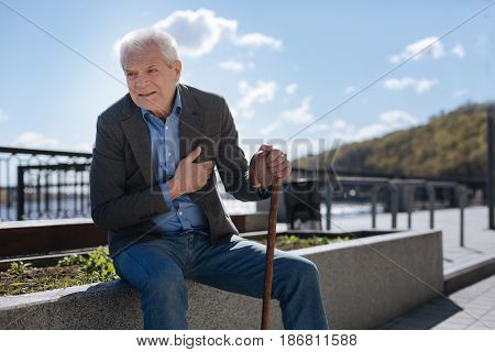 Hopeless pensioners. Old sad terrified man sitting on the flowerbed looking into the horizon and hoping for better