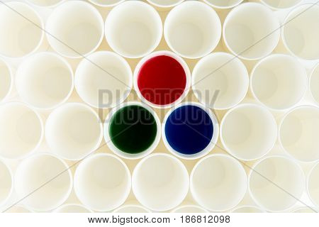 Top View Of Set Of Empty Plastic Cups And Cups With Red, Green And Blue Paints