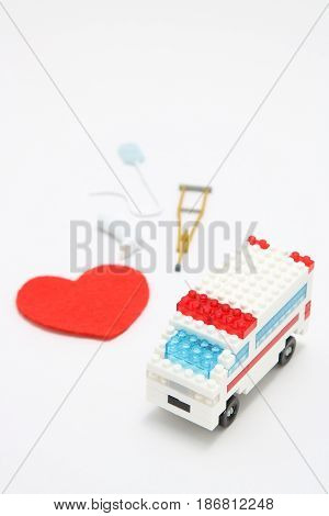 Toy ambulance car and abstract red heart on white background. Miniature drip,gibbs, and crutches. Health, medicine, and cardiology concept.  Charity, health care, donation concept.