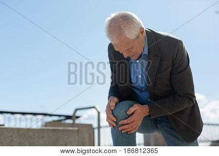 Our body can tell us a lot. Dismal frustrated old man raising himself onto his knee holding hands on it while feeling terrible pain