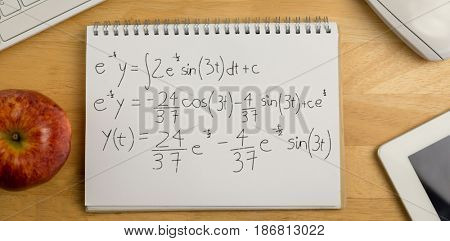 Calculations against black background against overhead of notepad and technology