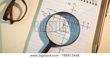 Maths pattern against black background against magnifying glass on notepad amidst pen and eyeglasses