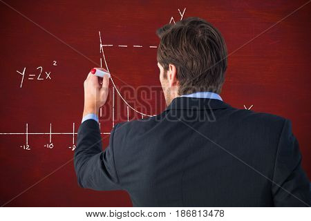 Rear view of businessman standing and writing against brown blackground