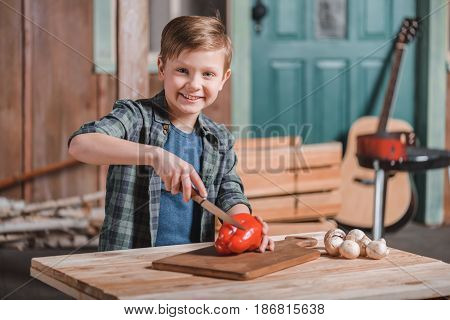 kid boy cutting bell pepper with knife on desk at backyard cooking