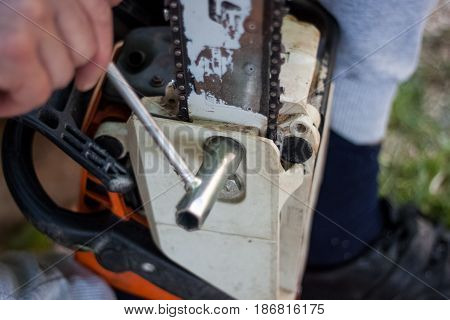 Woodman Made A Stop In The Cutting Of Trees To Sharpen And Tighten The Chain Of Chainsaws, Hand With