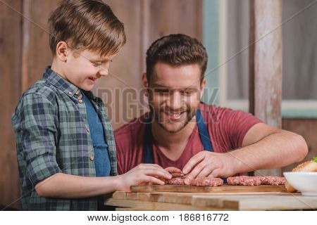 Happy Father And Son Cooking Meat Patties Together, Dad And Son Cooking Concept